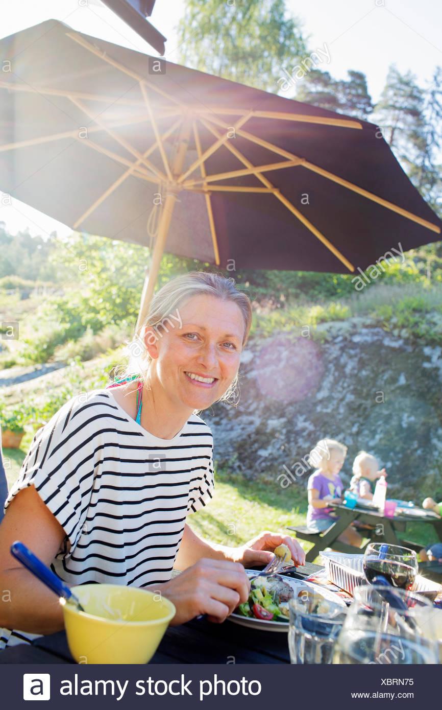 Donna sorridente di mangiare all'aperto Immagini Stock
