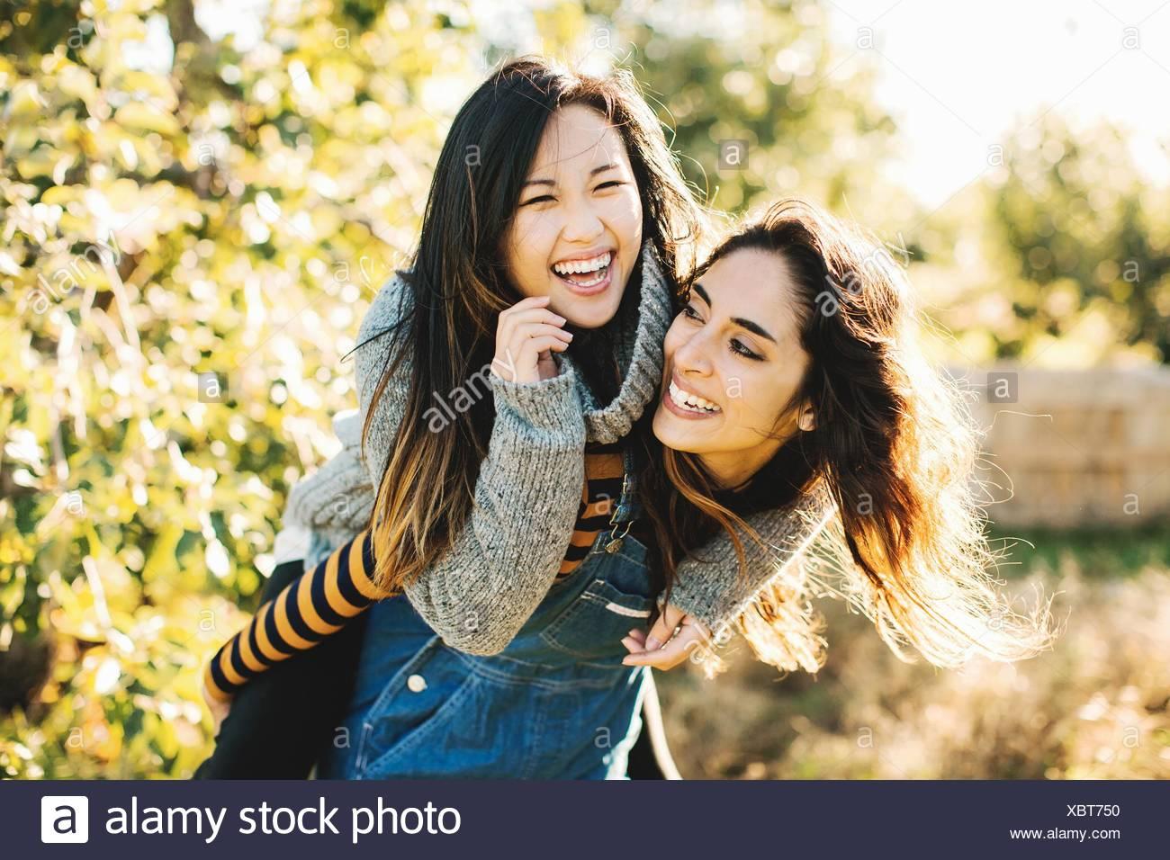 Giovane donna dando amico piggyback ride, all'aperto Immagini Stock