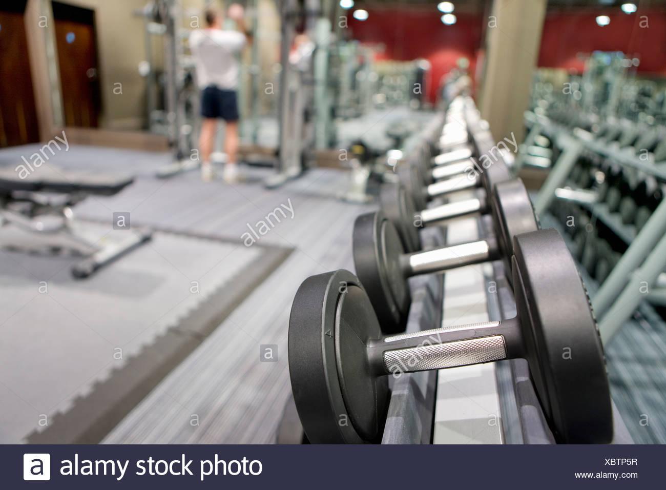 Rack di manubri nel club salute con uomo sollevamento pesi in background Immagini Stock