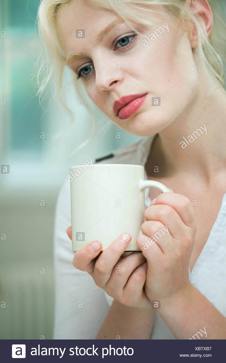 Malinconica cerca donna giovane con un caffè Immagini Stock