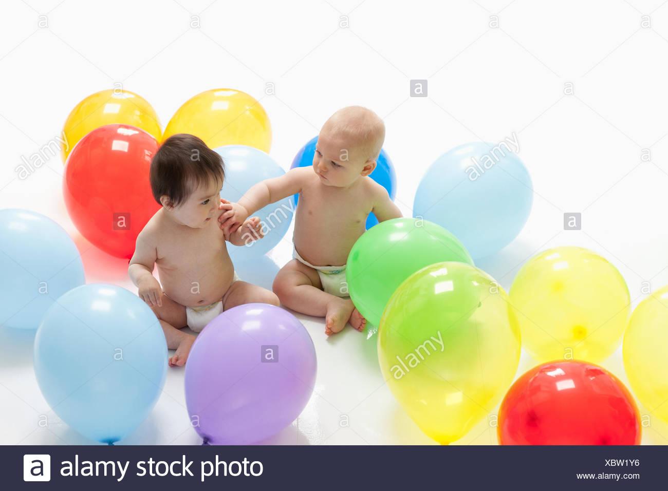 I neonati con palloncini sul pavimento Immagini Stock