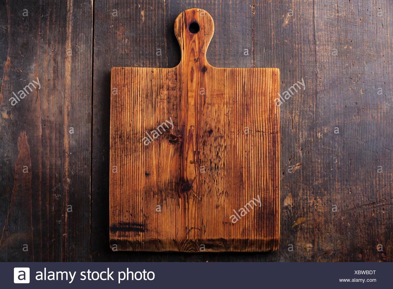 Tritare il tagliere in legno scuro dello sfondo Immagini Stock