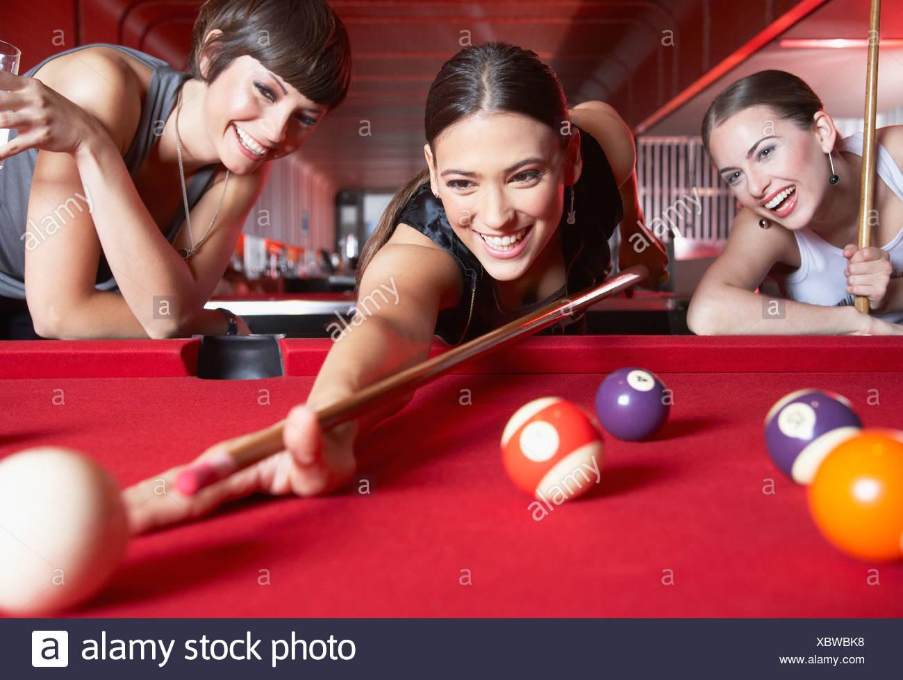 Tre donne giocando a biliardo e sorridente Immagini Stock