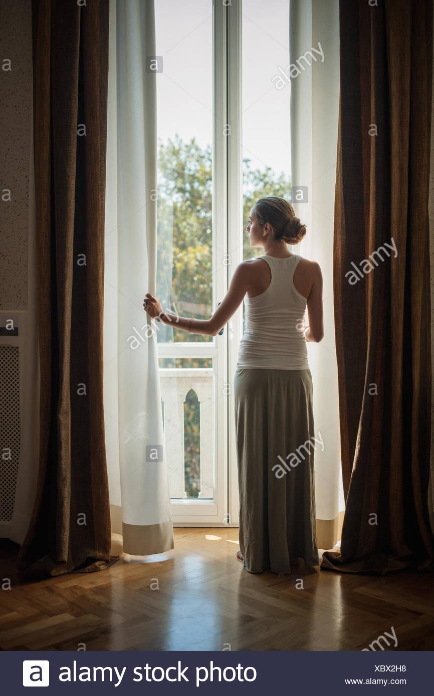 Elegante giovane donna guardando fuori della stanza di seduta windows Foto Stock