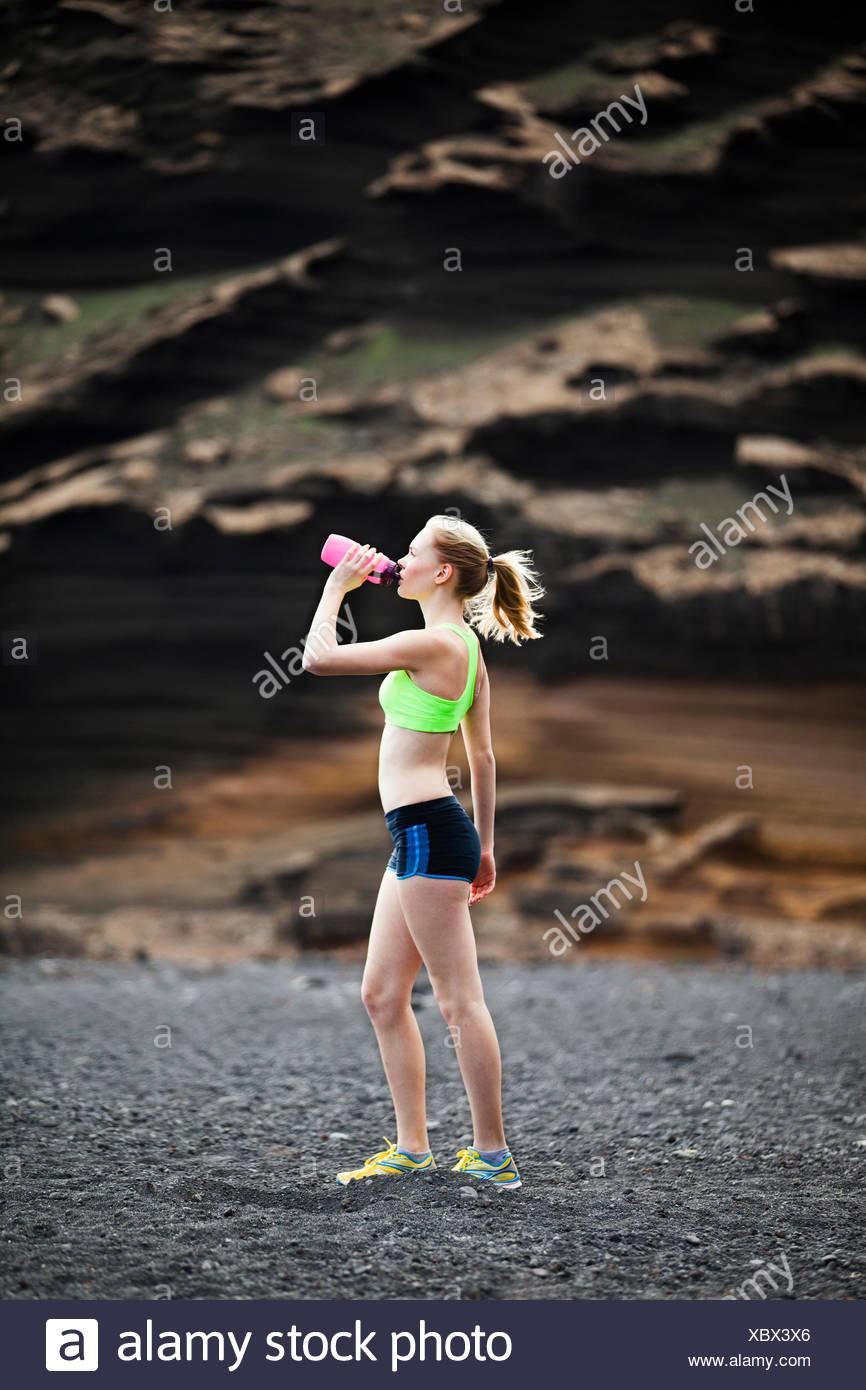 Donna acqua potabile, acceso, jogging Immagini Stock