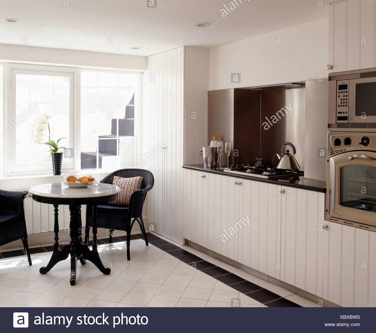 Cucina Bianca Moderna Con Tavolo Antico.Sedia In Vimini E Piccolo Tavolo Antico In Una Moderna Cucina Bianca