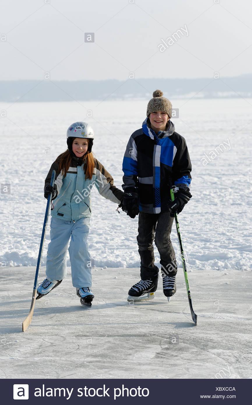 Ragazzo e una ragazza la riproduzione di hockey su ghiaccio, vicino San Heinrich, il lago di Starnberg, cinque laghi, Alta Baviera, Baviera Immagini Stock
