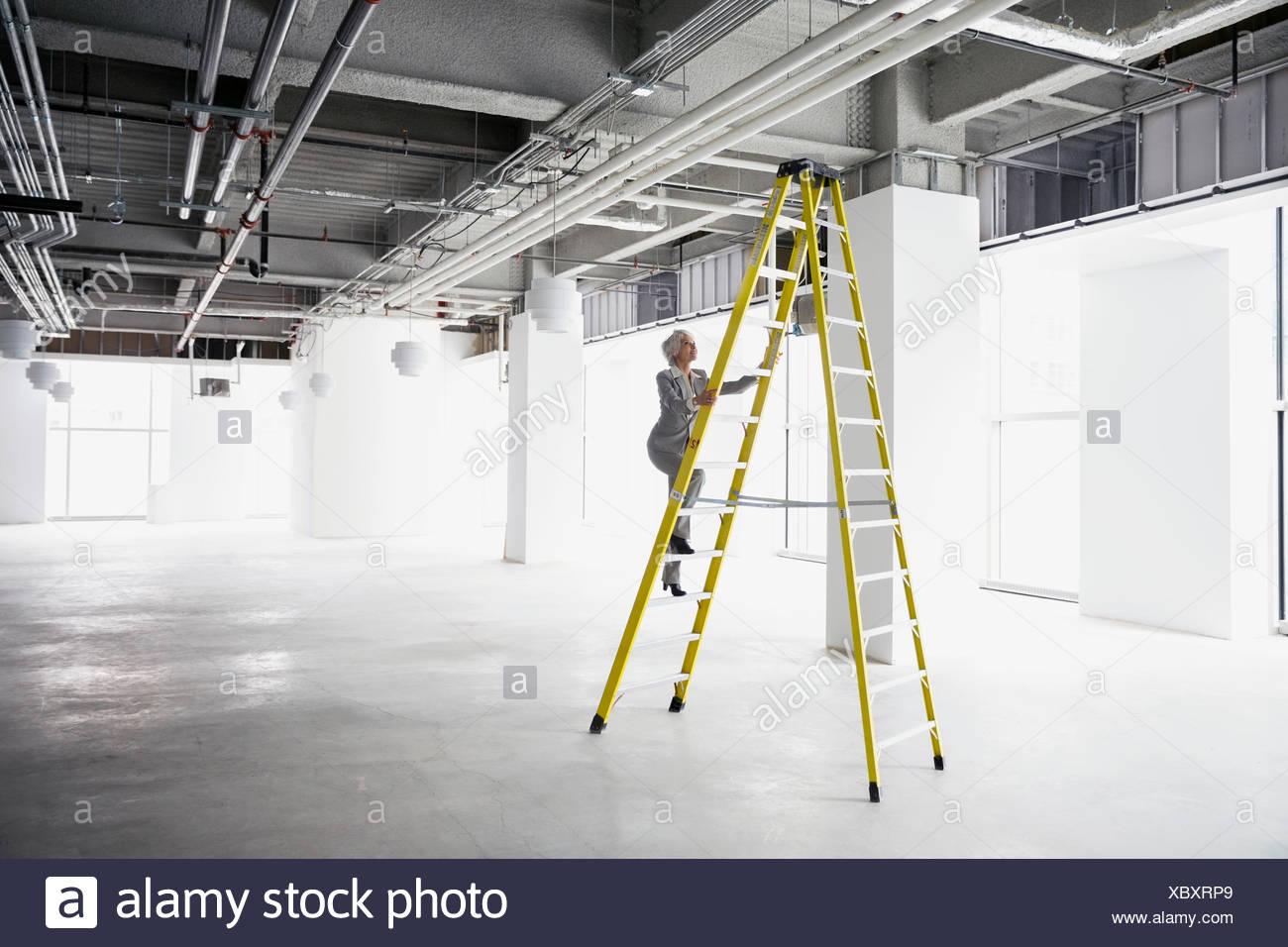 Imprenditrice scaletta di arrampicata in ufficio vuoto Immagini Stock