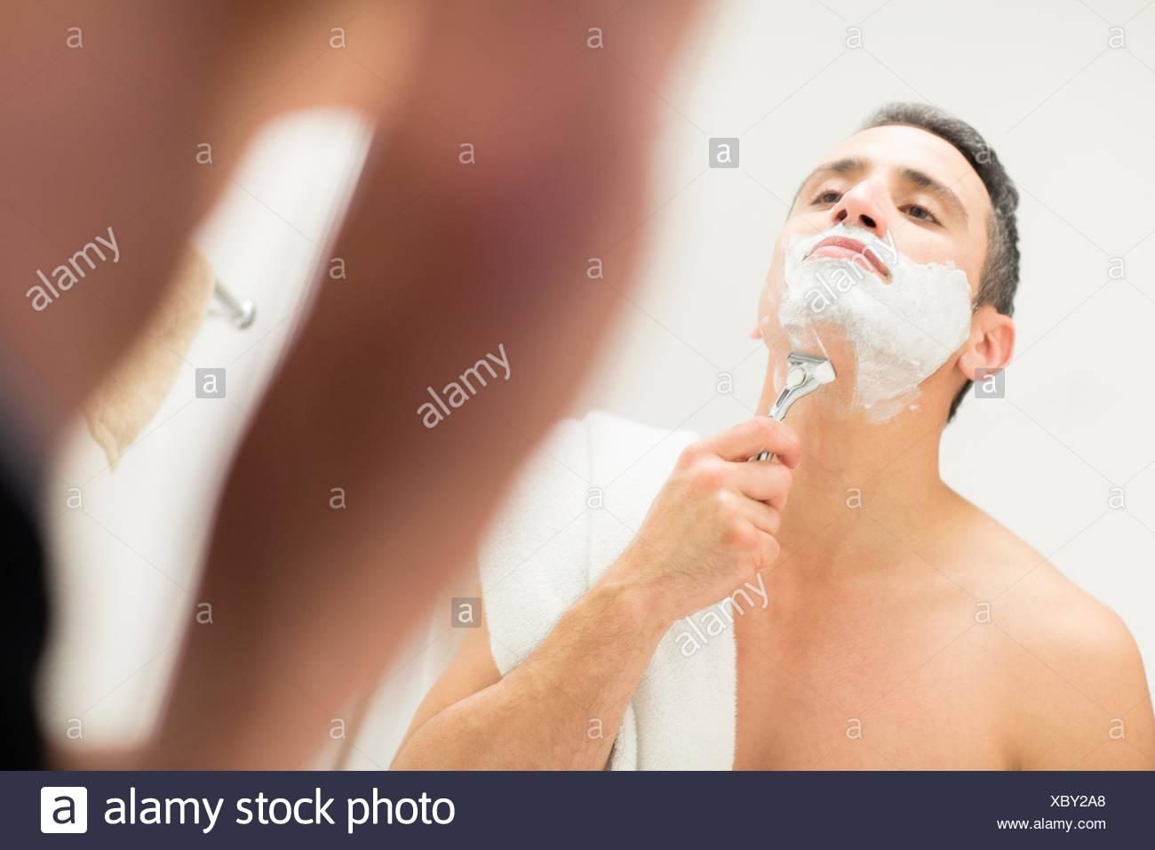 Metà uomo adulto, guardando in uno specchio, la rasatura Immagini Stock