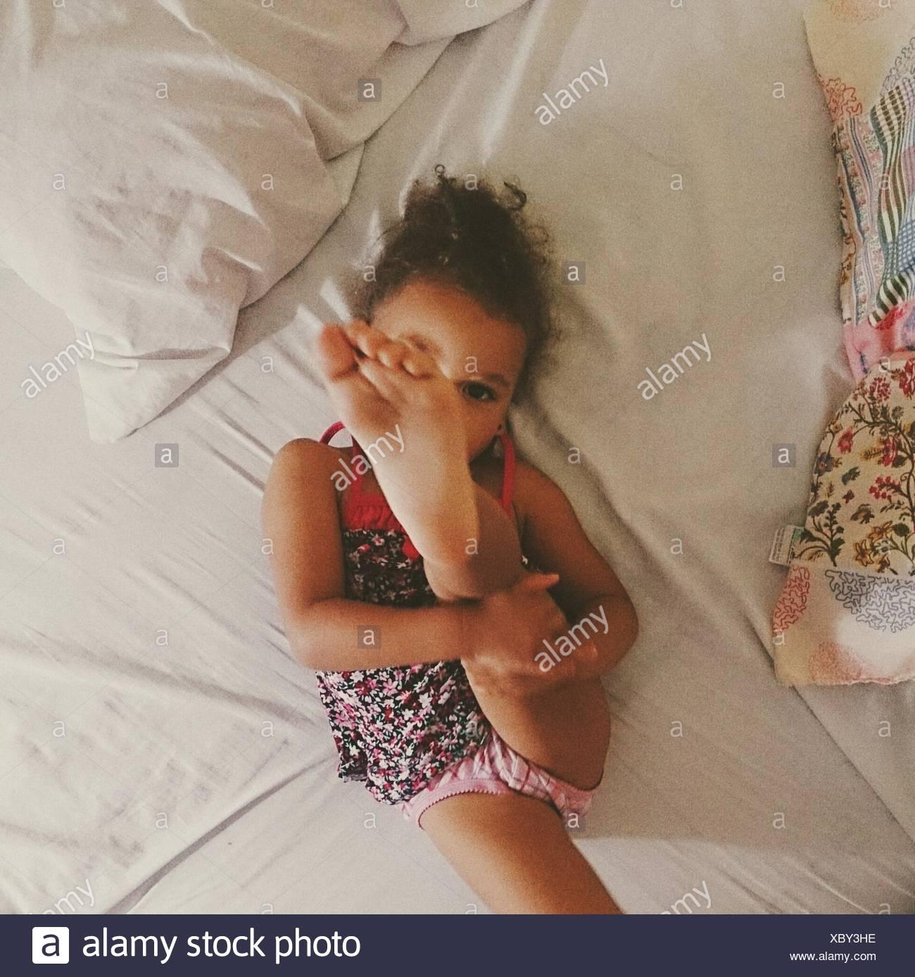 Angolo di Alta Vista della ragazza con piedi durante i momenti di relax sul letto Immagini Stock