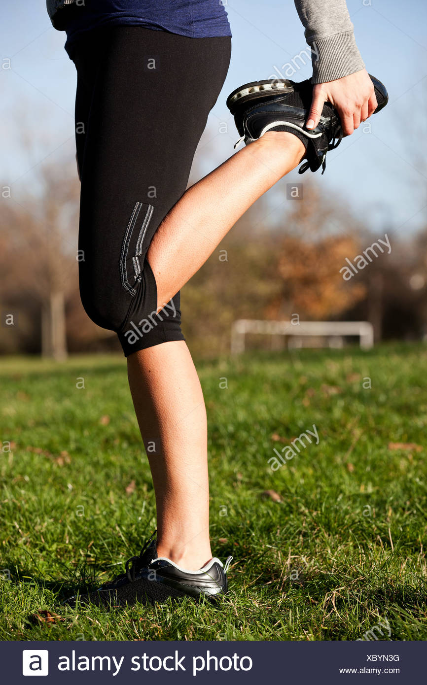 Metà donna adulta esecuzione warm-up esercizi nel parco, sezione bassa Immagini Stock