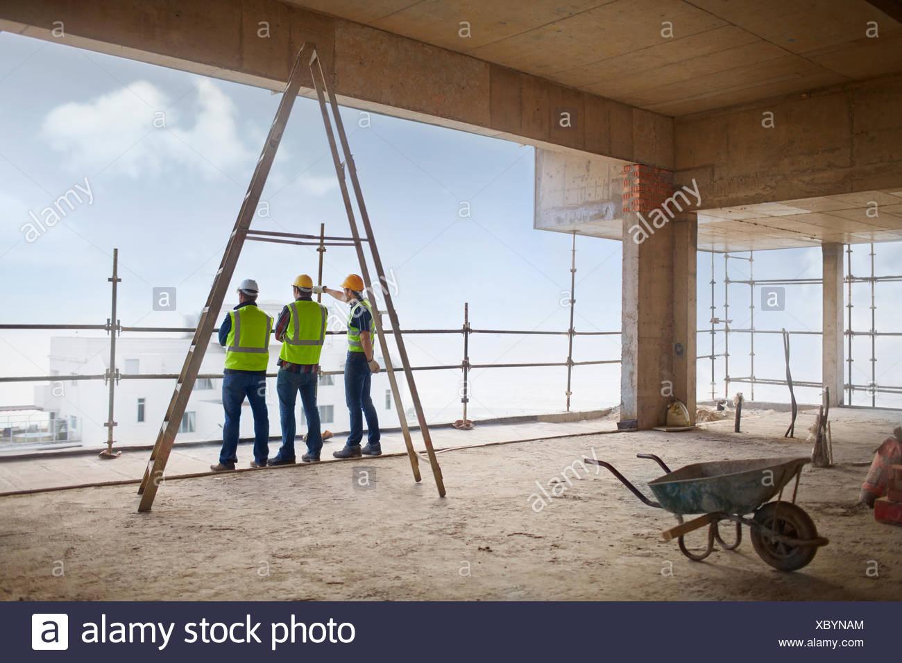 Lavoratori edili a highrise sito in costruzione Immagini Stock