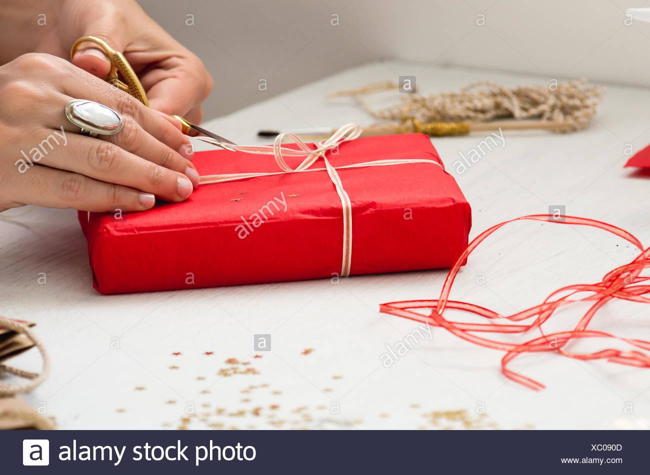 Immagine ritagliata di mano il nastro di taglio sul dono a tavola Immagini Stock