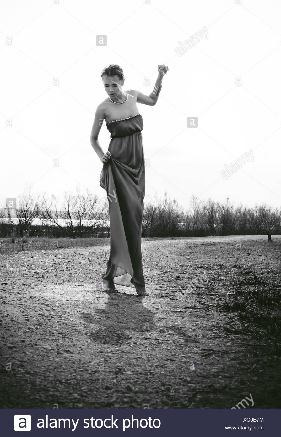 Donna che indossa abiti lunghi in piedi in Prato Immagini Stock