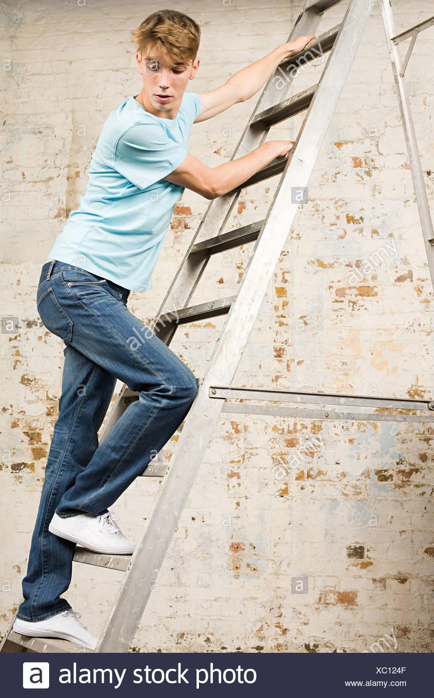 Ragazzo adolescente su una scala Immagini Stock