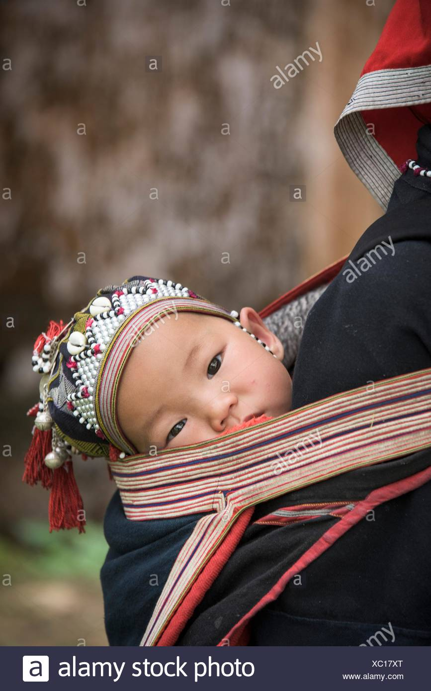 Il Vietnam, Sapa, Rosso Zao tribù, baby sulla madre del back Foto Stock