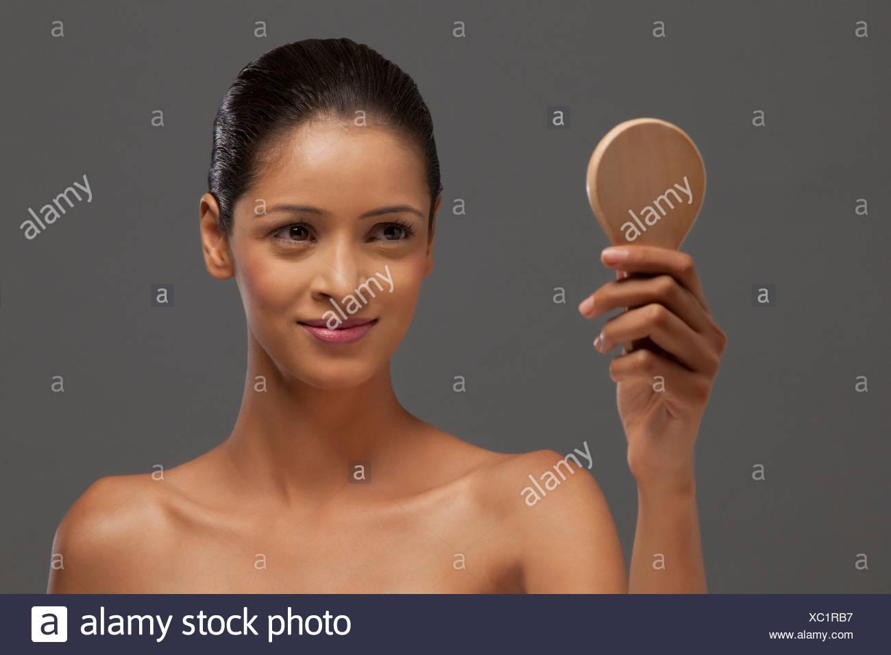 Close-up di donna sorridente guardando lo specchio a mano Immagini Stock