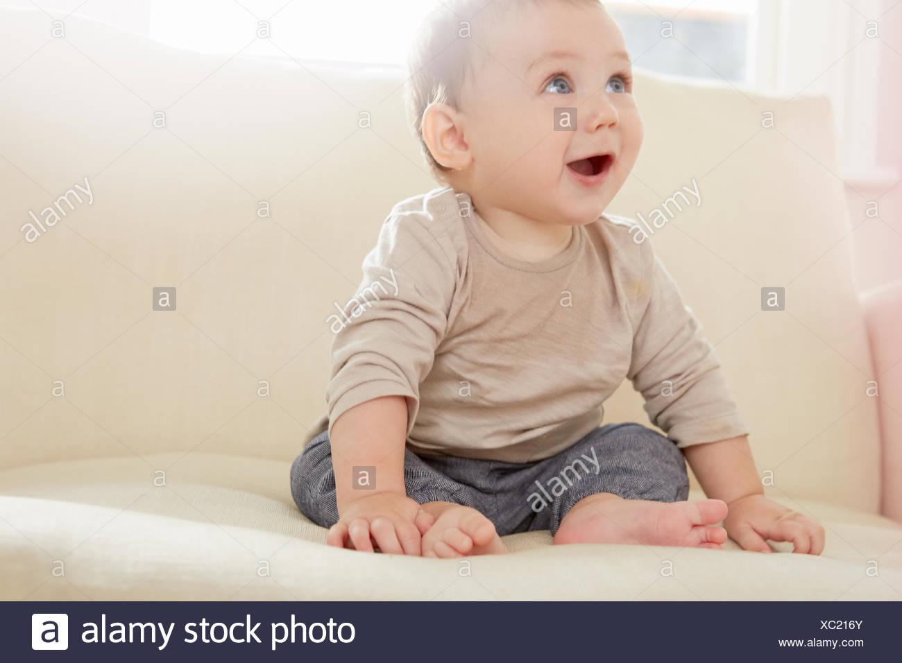 Baby boy guardando verso l'alto dal divano Immagini Stock