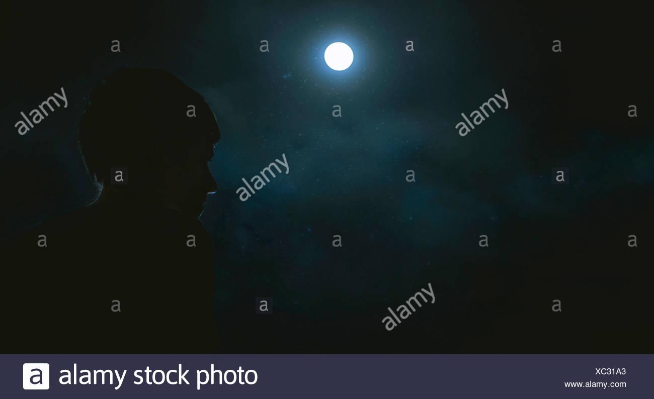 Silhouette di un ragazzo (12-13) al chiaro di luna Immagini Stock
