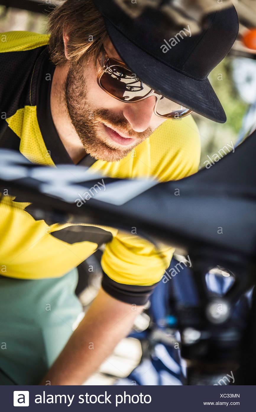 Chiusura del giovane maschio mountain biker controllo bike Immagini Stock