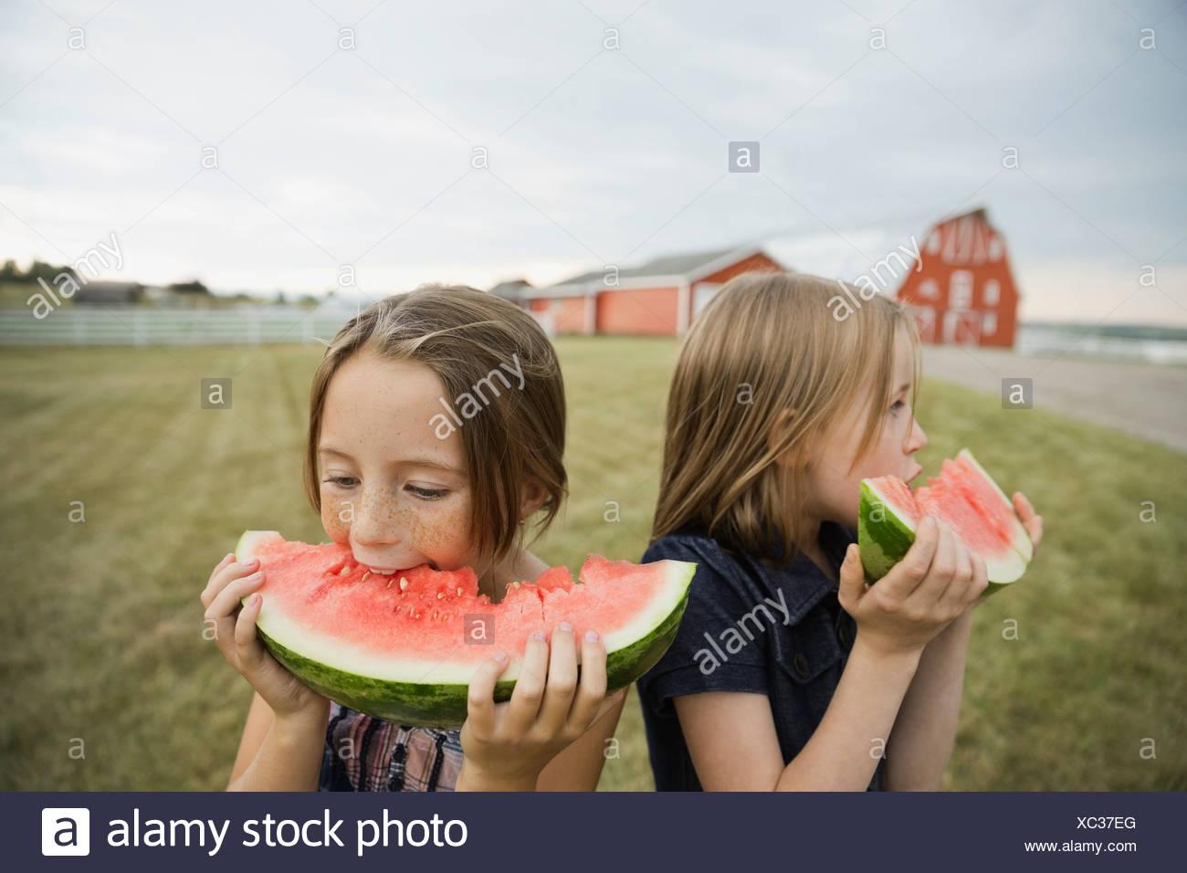 Ragazze mangiando anguria all'aperto Immagini Stock