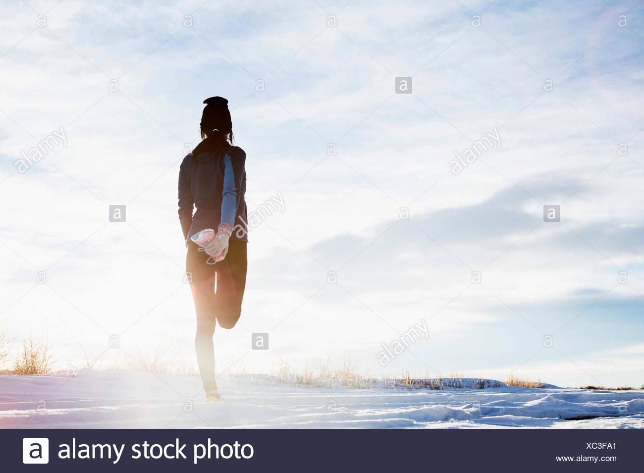 Donna matura stiramento nella neve Immagini Stock