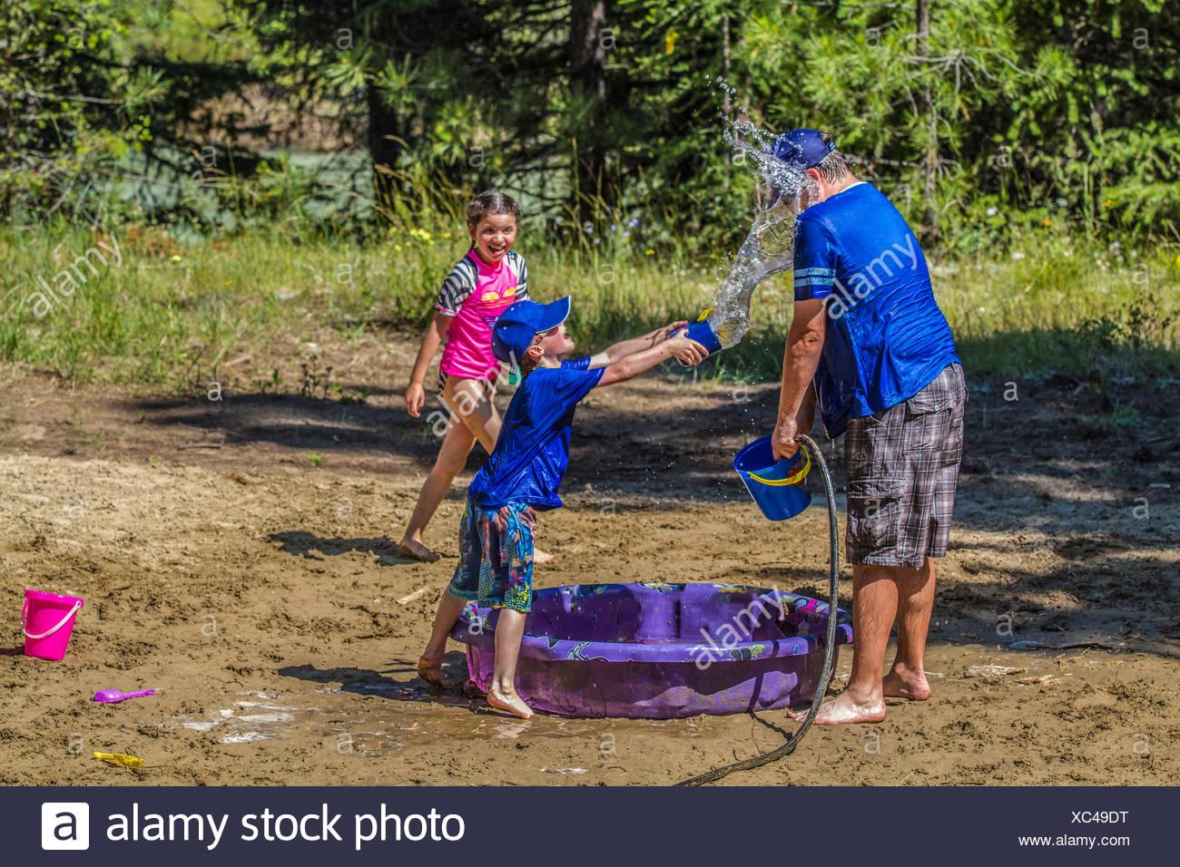Per adulti e bambini in acqua playfull lotta , su una calda e soleggiata giornata estiva. Cranbrook, British Columbia, Canada. Foto Stock