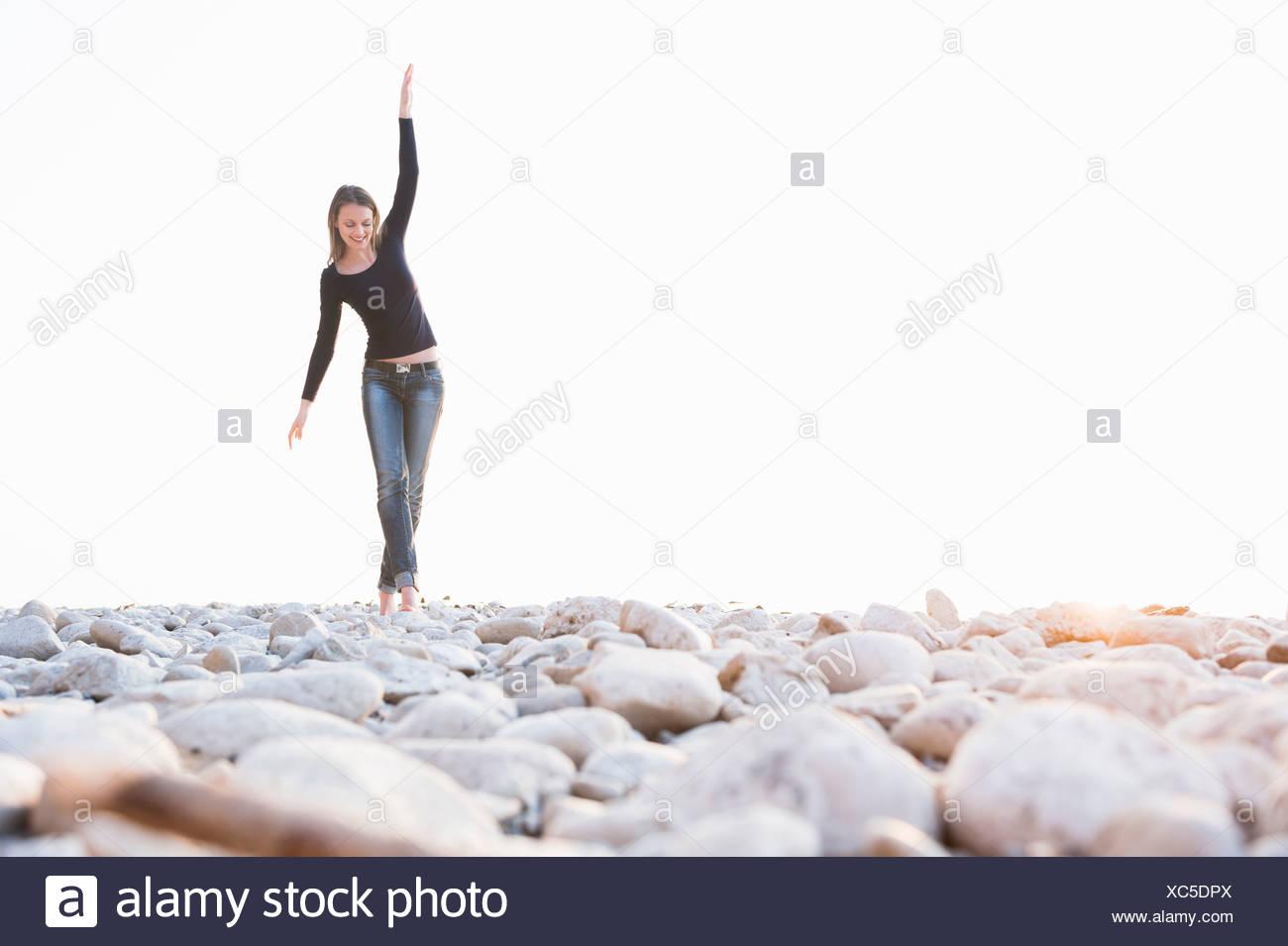 Giovane donna camminare a piedi nudi sulle pietre a costa Immagini Stock