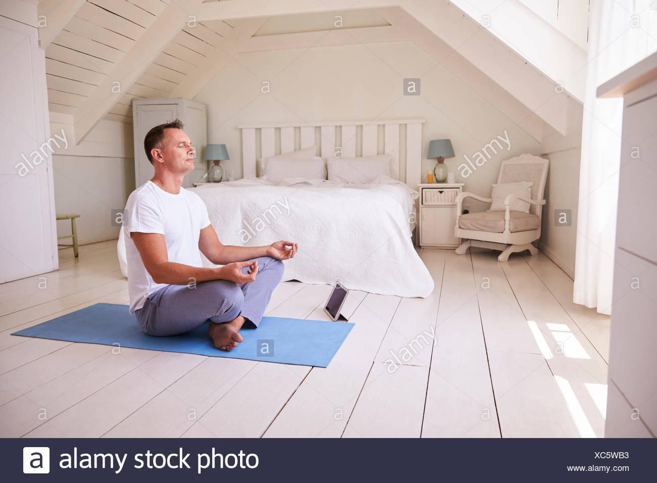 Uomo maturo con tavoletta digitale utilizzando la meditazione di app in camera da letto Immagini Stock
