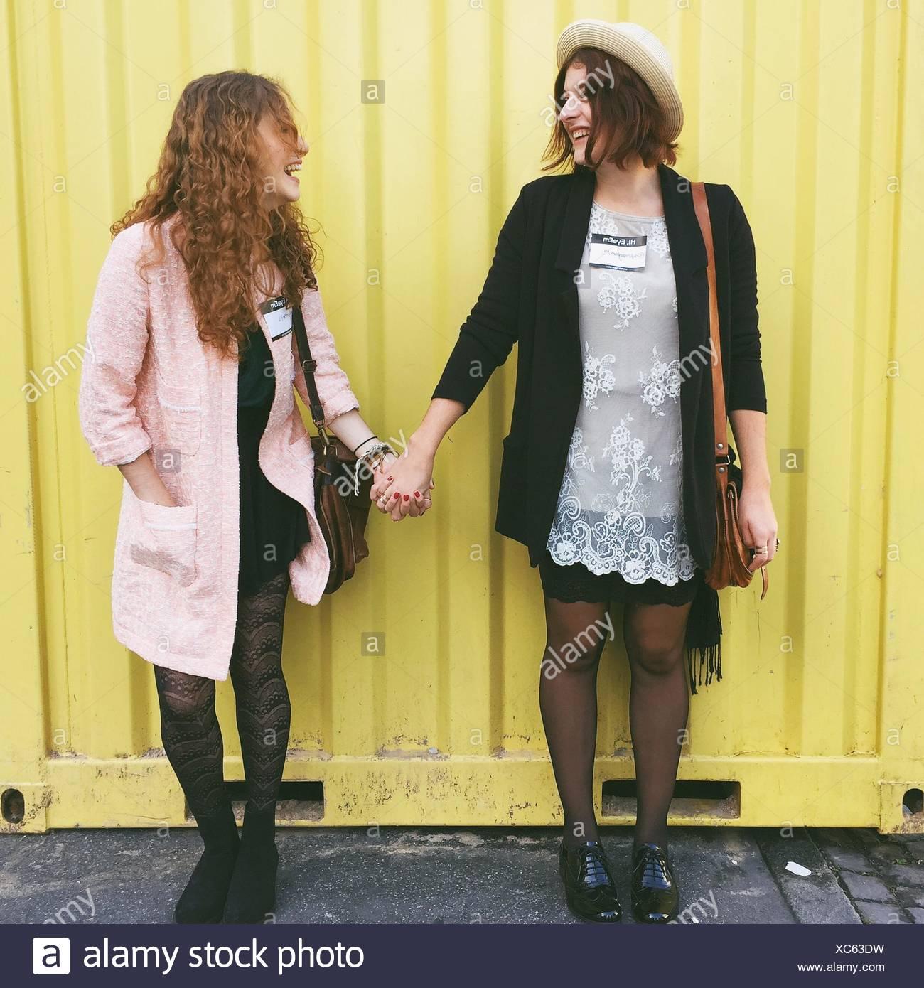 Allegro amico tenendo le mani mentre in piedi contro la parete metallica Immagini Stock