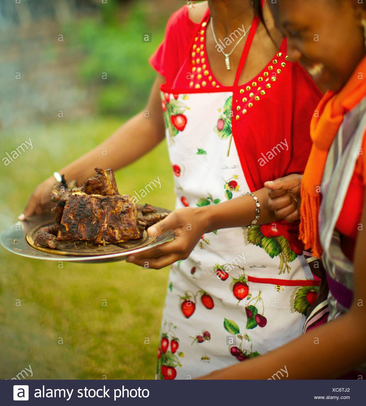 Giovani donne che serve carne cotta, KwaZulu-Natal, Sud Africa Immagini Stock