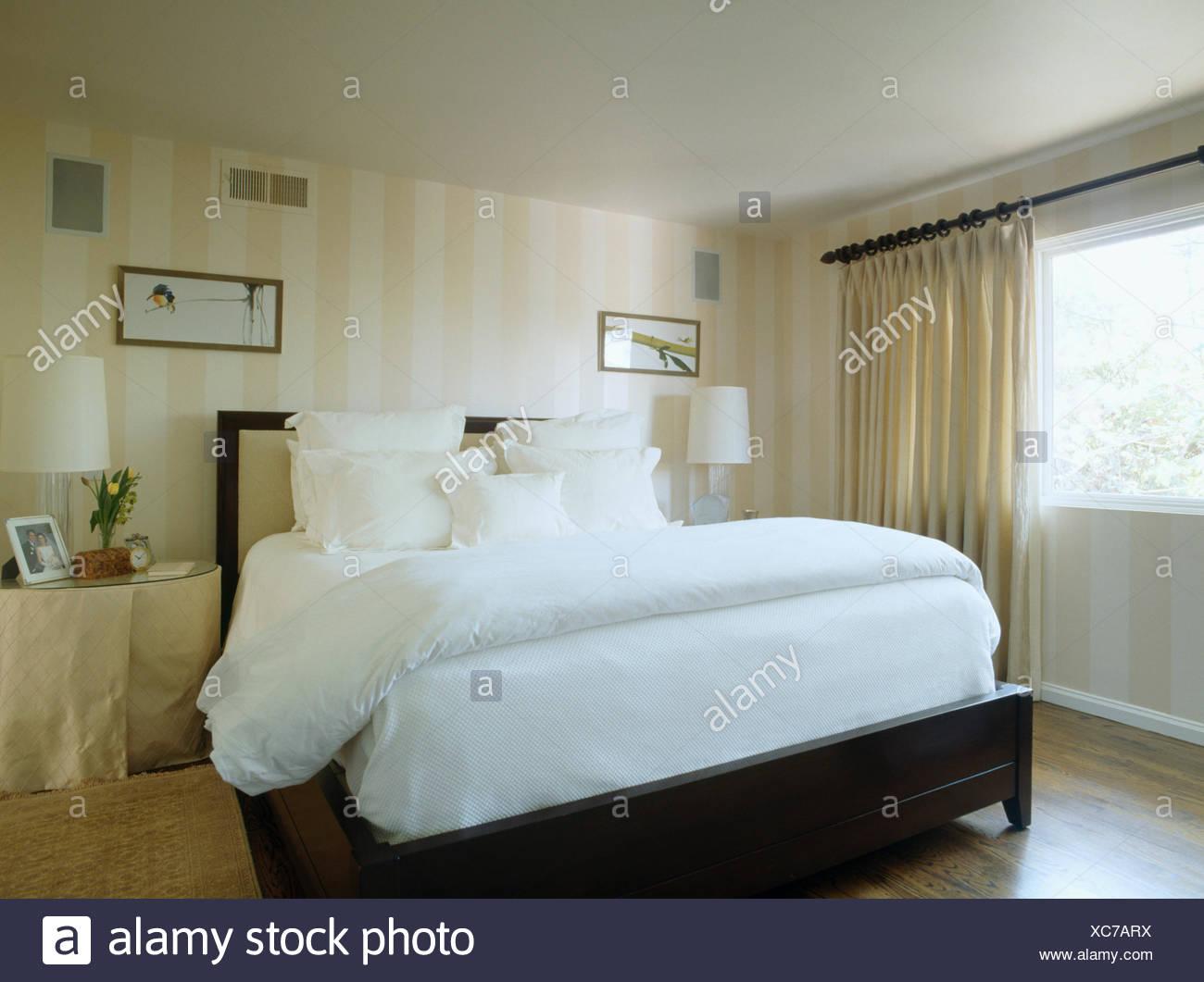 Il piumone bianco e cuscini sul letto in camera da letto moderna con neutro tende e carta da - Carta da parati camera da letto moderna ...