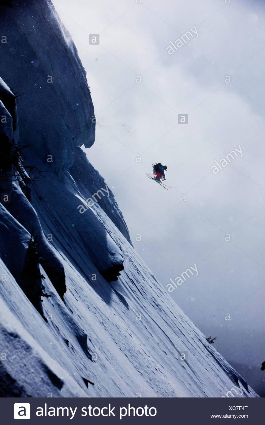 Uno sciatore salta fuori da un enorme cornicione in Colorado. Immagini Stock