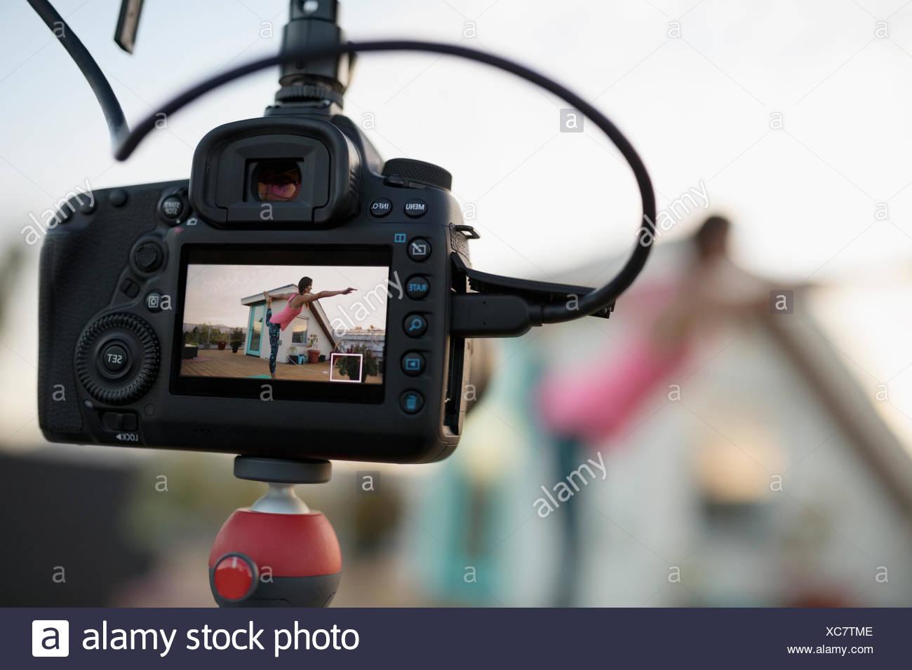 Vista attraverso il mirino della fotocamera femminile di istruttore yoga di filmare re posizione del signore della danza Immagini Stock