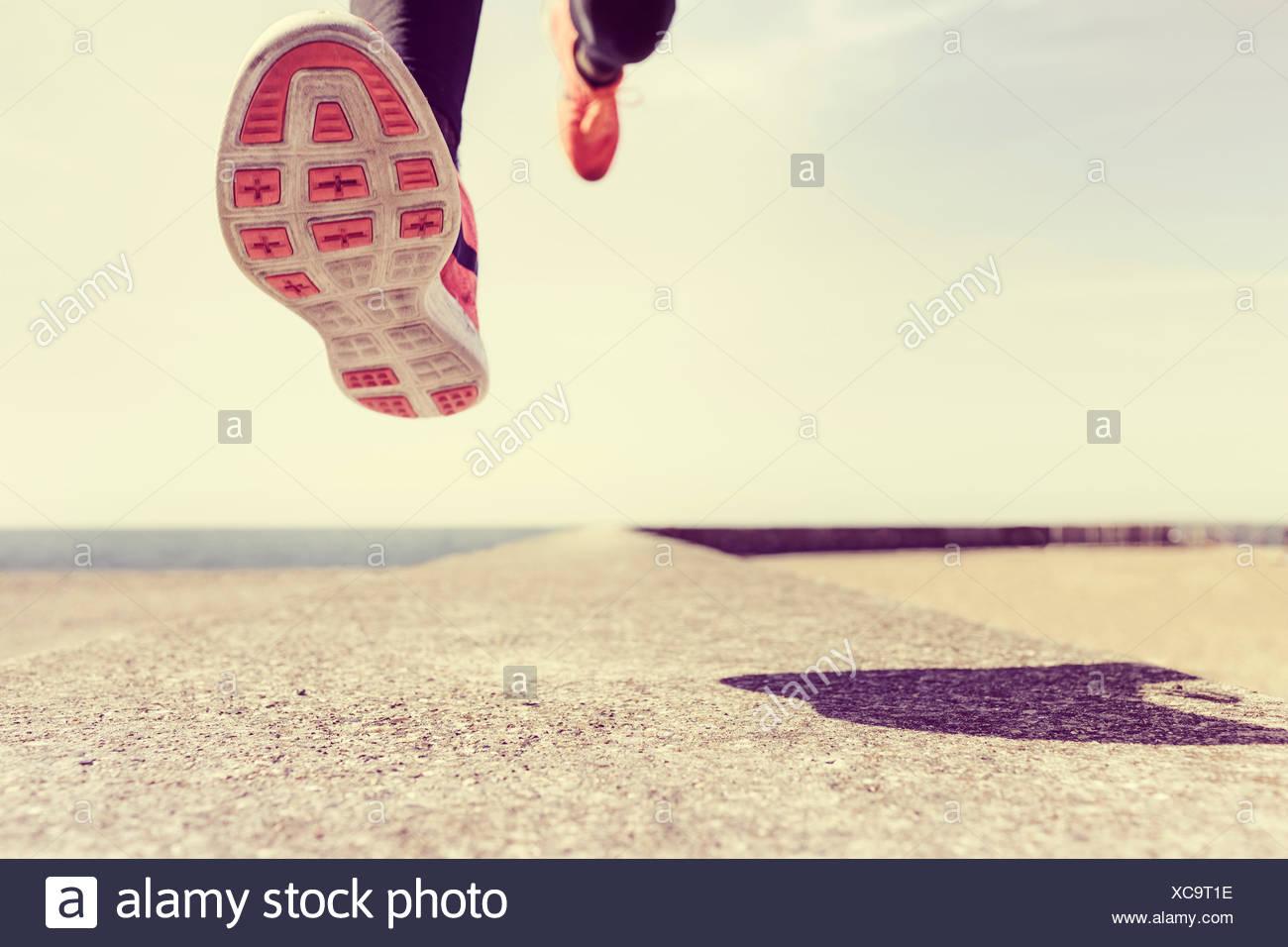 Giovane uomo che corre all'aperto, metà aria, sezione bassa Immagini Stock