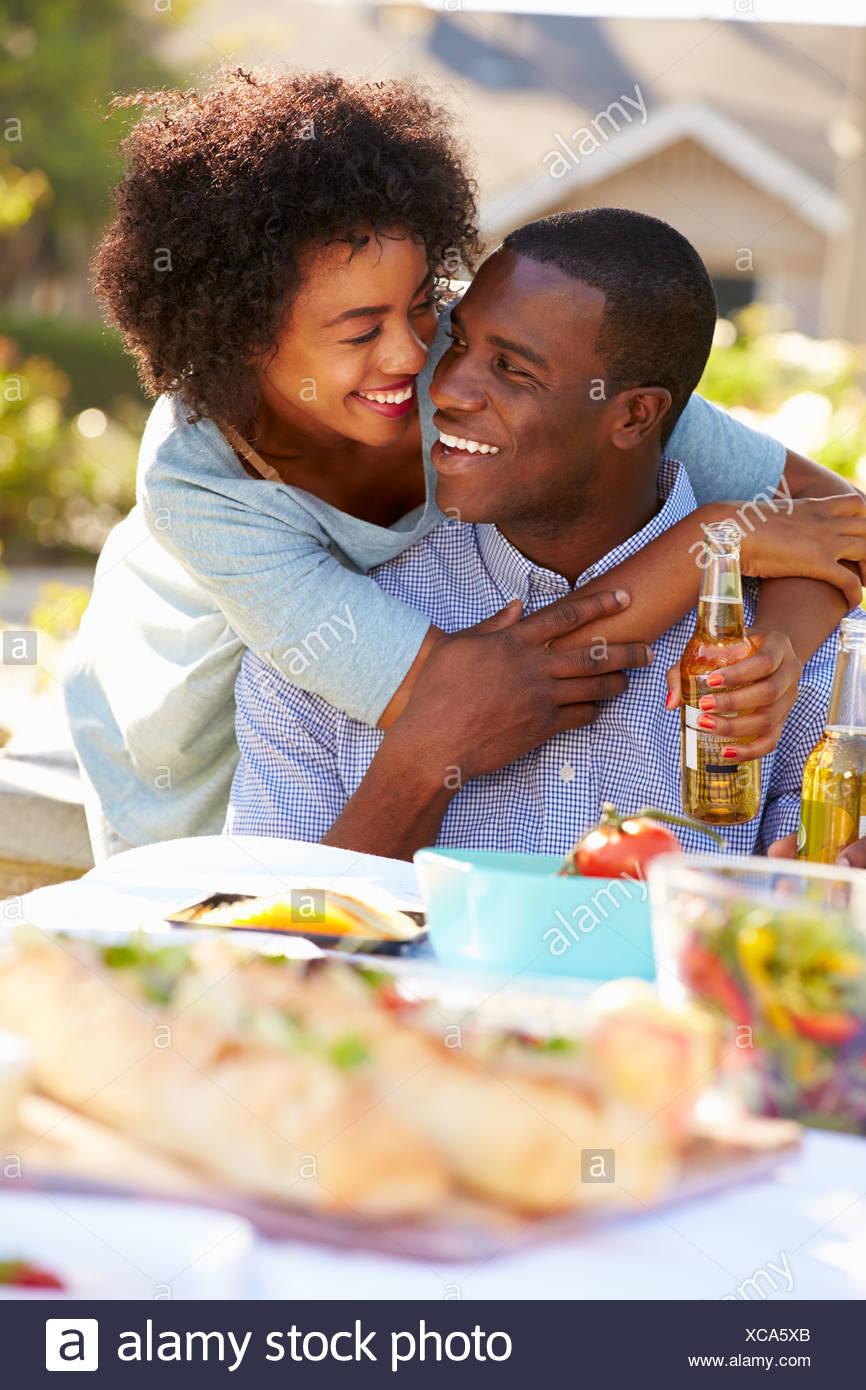 Coppia romantica gustando pasti all'aperto in giardino Immagini Stock