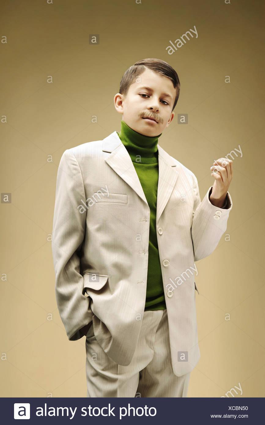 Ragazzo giovane vestito in tuta color beige con baffi finti Immagini Stock