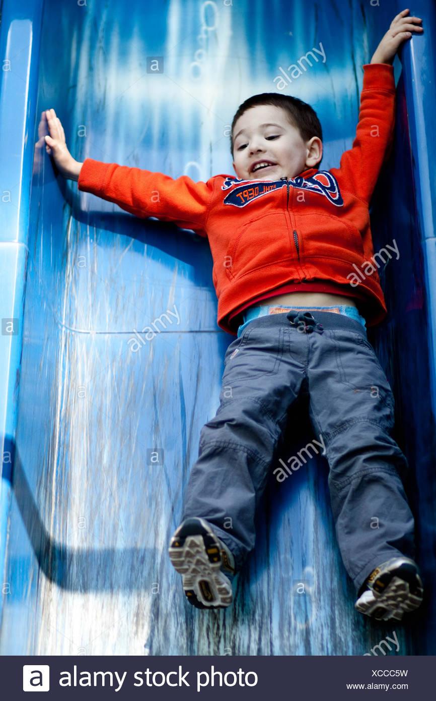 Ragazzo scivolare giù scorrere nel parco giochi Immagini Stock