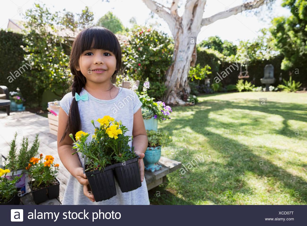 Ritratto sorridente ragazza con vasi di fiori Immagini Stock
