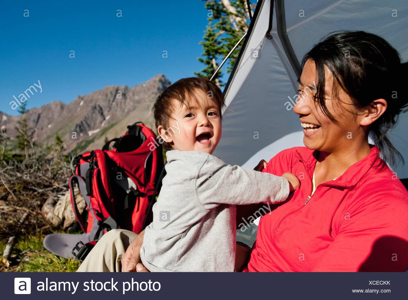 Madre veglia figlio di 14 mesi giocare nel prato di camp. Backpacking trip Maroon Bells in Snowmass deserto fuori Aspen Immagini Stock