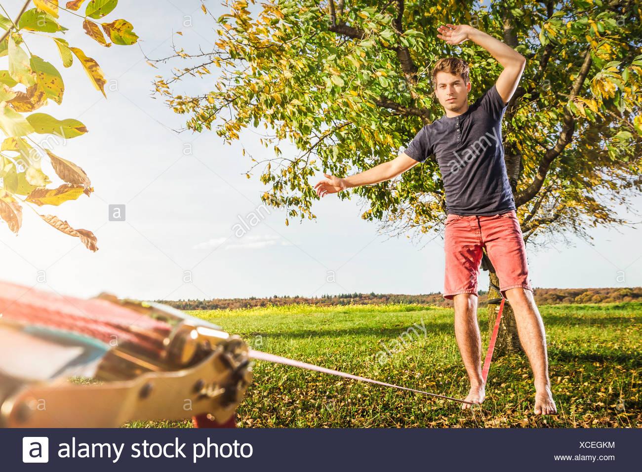 Ritratto di giovane uomo equilibrato sul slackline Immagini Stock