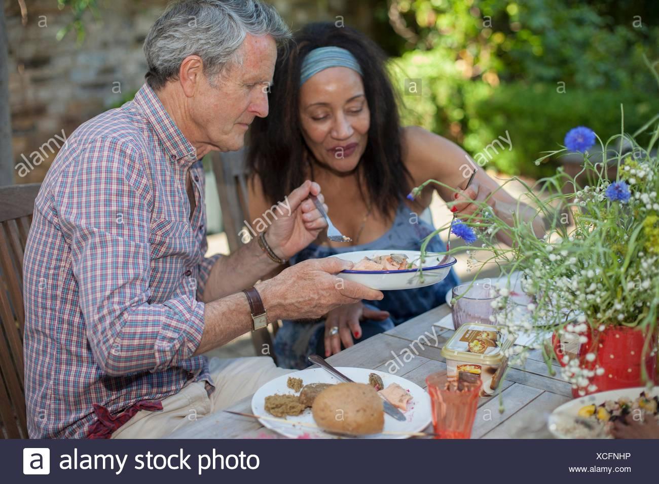 Coppia senior di mangiare pasti all'aperto Immagini Stock
