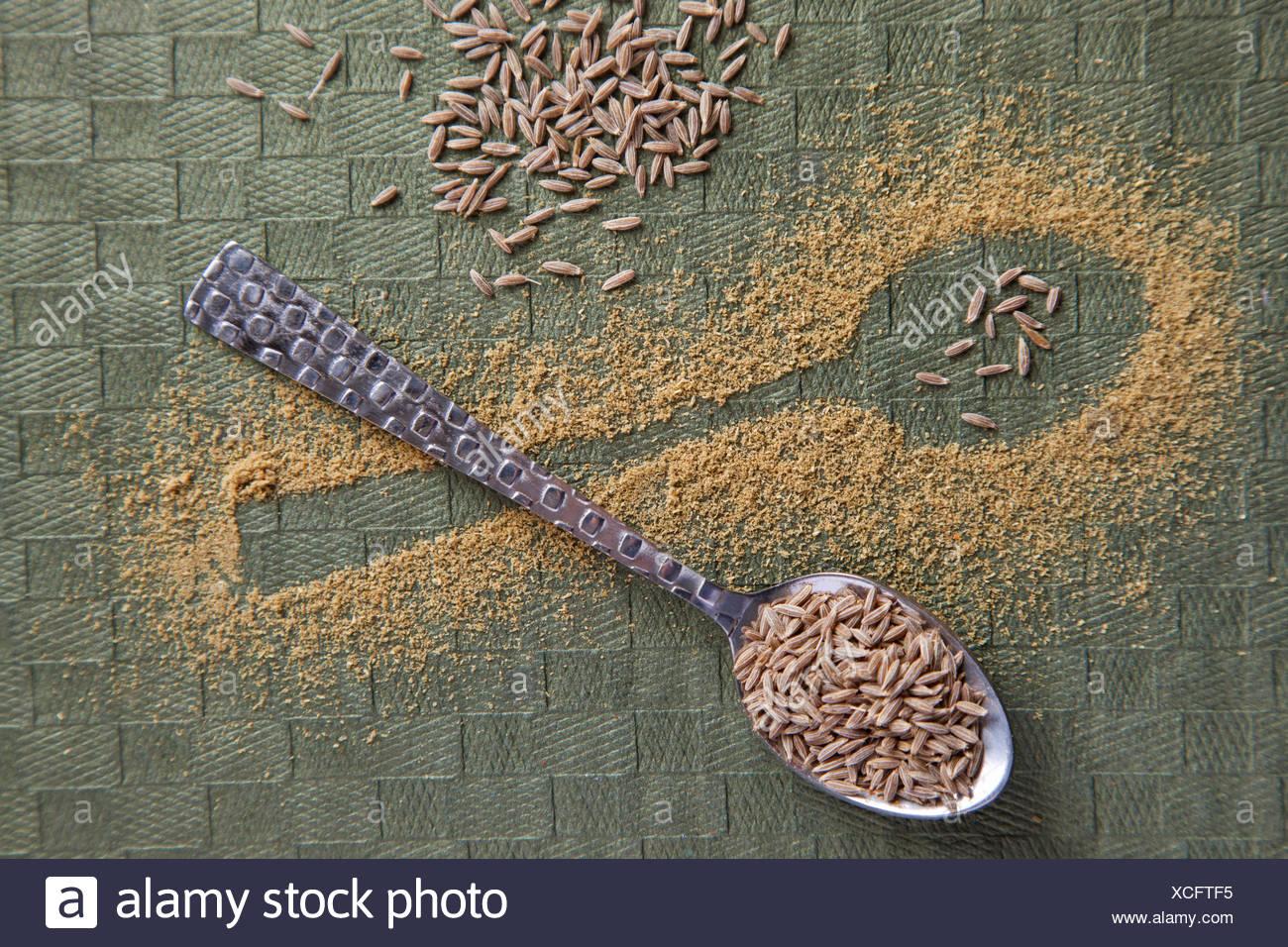 La forma di un cucchiaio in casualmente disperse il cumino in polvere e semi di cumino sul cucchiaio Immagini Stock