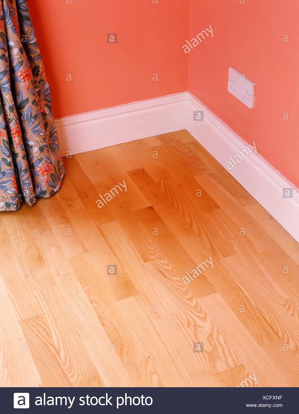 Battiscopa In Legno Bianco angolo della stanza con laminato pavimento in legno bianco e