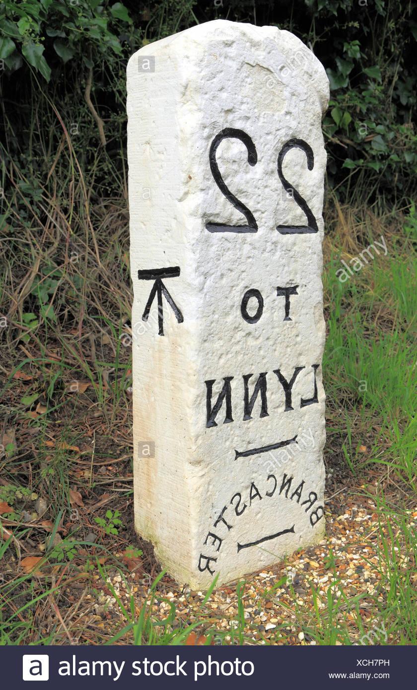 Pietra miliare, Brancaster a Kings Lynn, Norfolk, old English Turnpike road strade pietre miliari, 22 miglia a Lynn, ampio segno di freccia Immagini Stock