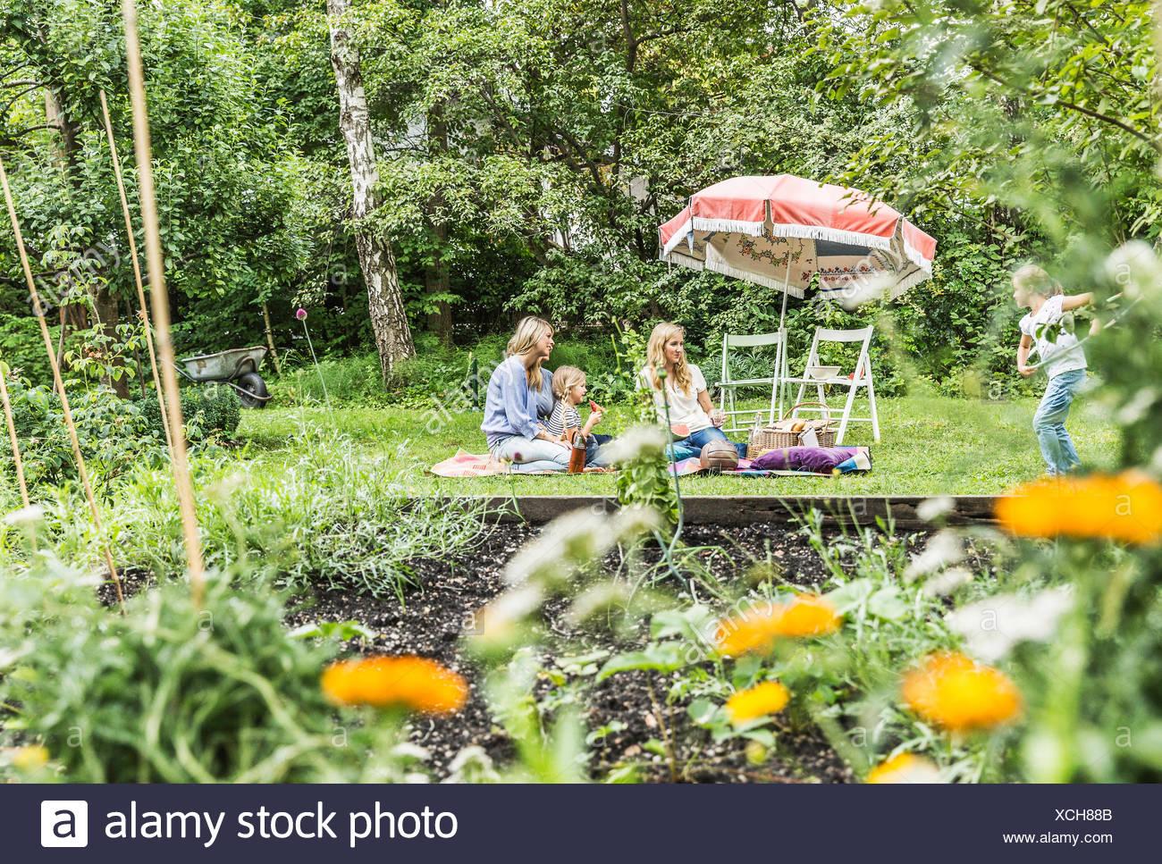 Due donne e due ragazze picnicing in giardino Immagini Stock