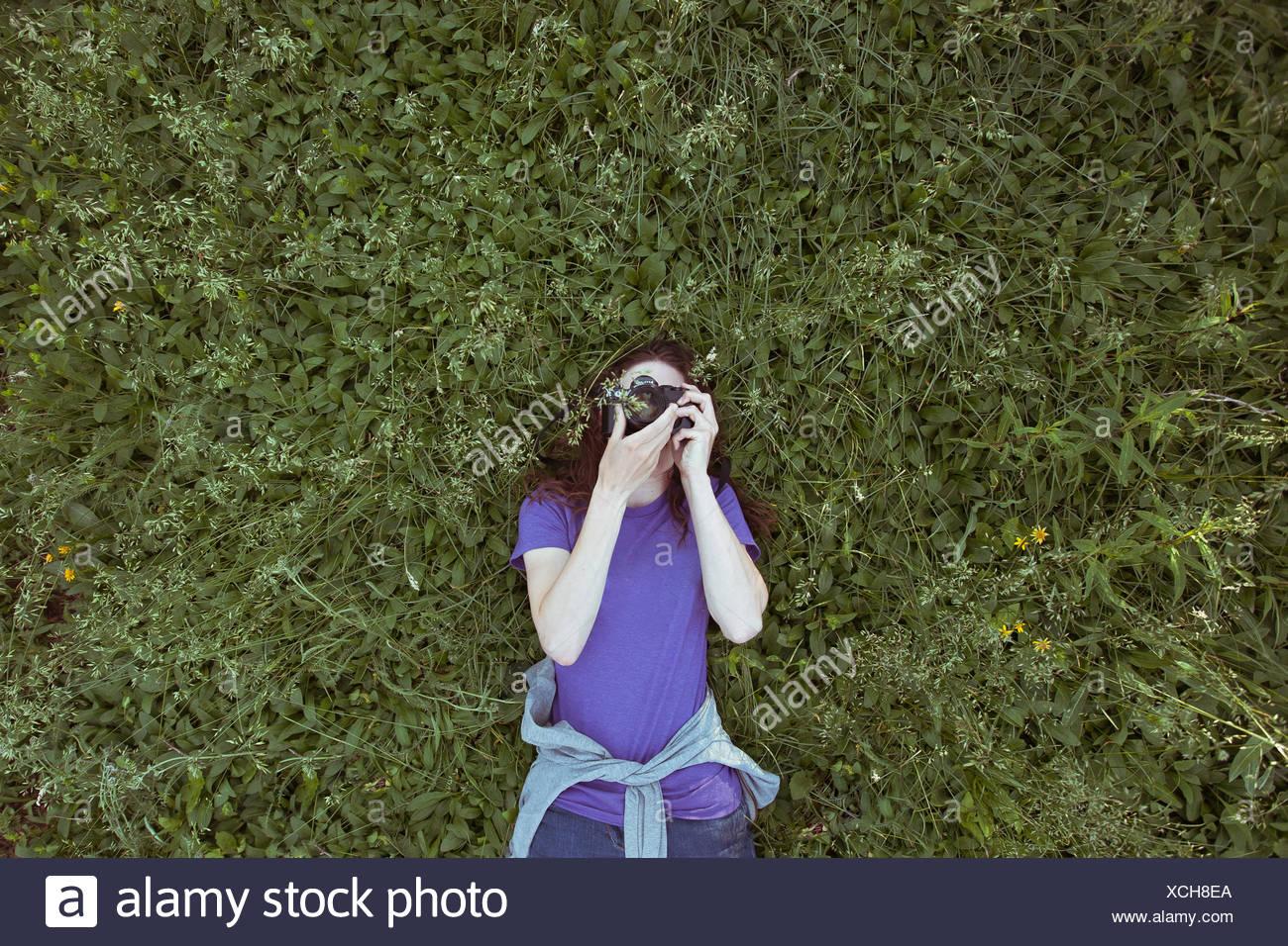 Donna sdraiata in erba fotografare sky Immagini Stock