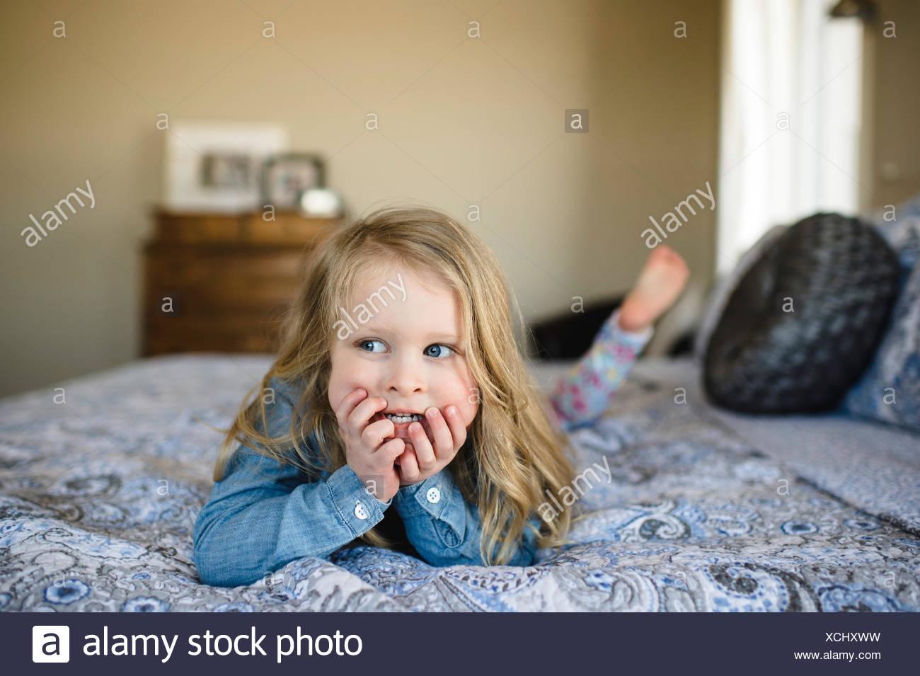 Ragazza distesa sul letto guardando lateralmente Immagini Stock