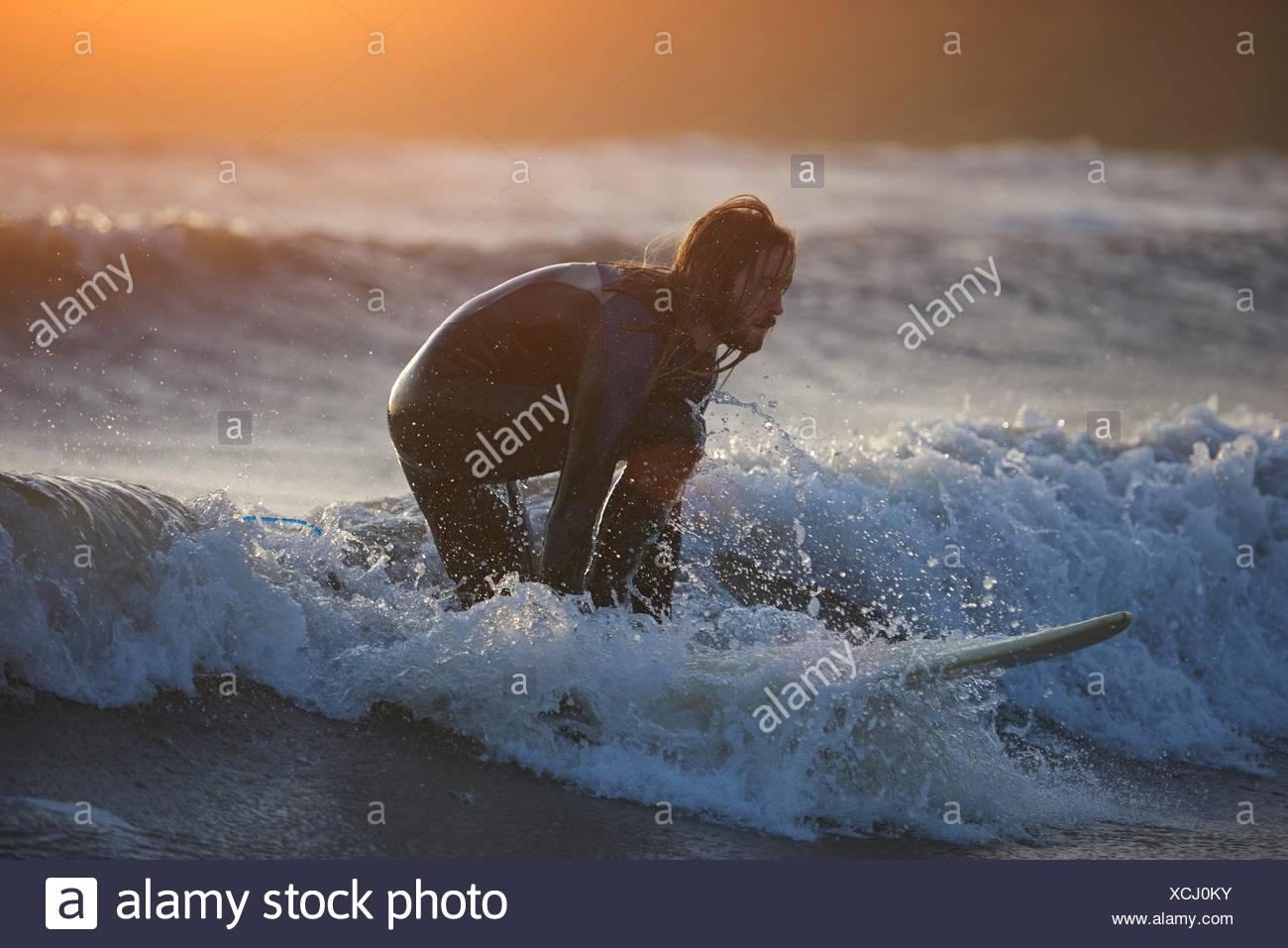 Giovane maschio surfer surf sulle onde dell'oceano, Devon, Inghilterra, Regno Unito Immagini Stock