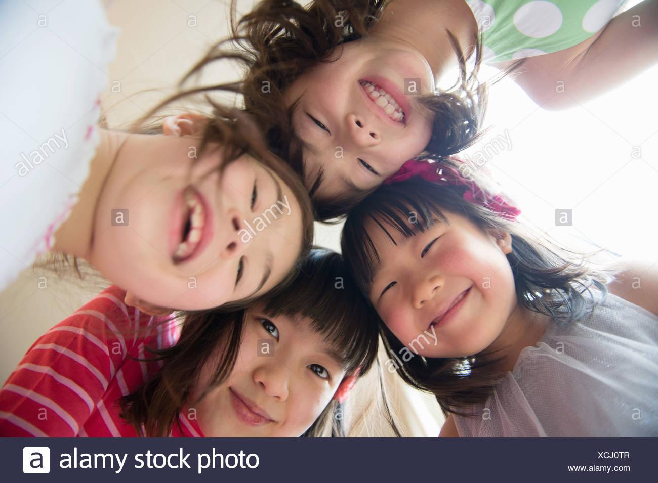 Ragazze in huddle guardando la telecamera, sorridente Immagini Stock